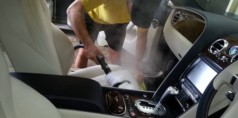 Leather seats are being cleaned with a steam cleaner
